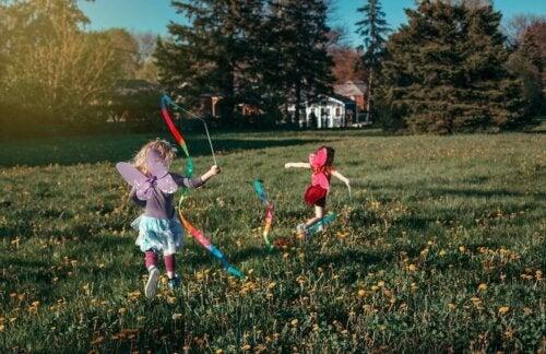 Des enfants courent au parc avec des déguisements de fée.