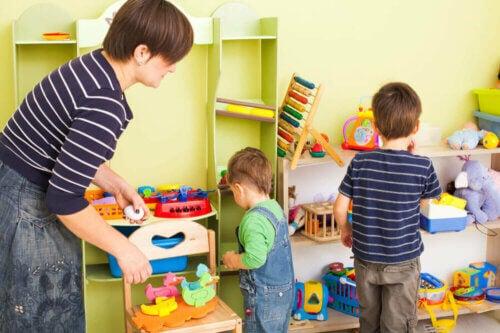 Des enfants qui rangent les jouets dans leur chambre avec maman.