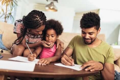 Deux parents qui aident leur jeune fille à faire ses devoirs.