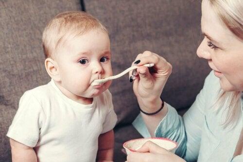Une maman qui donne à manger à son bébé à la petite cuillère.