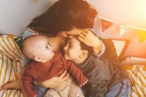 Une mère qui fait un câlin à ses deux enfants.