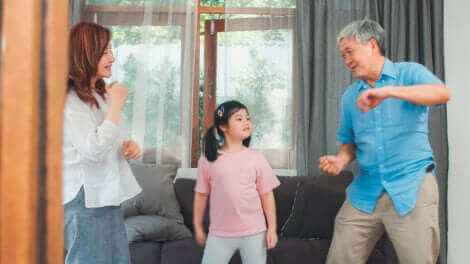 Des parents dansant avec leur fille.