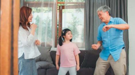 Une famille qui danse dans le salon.