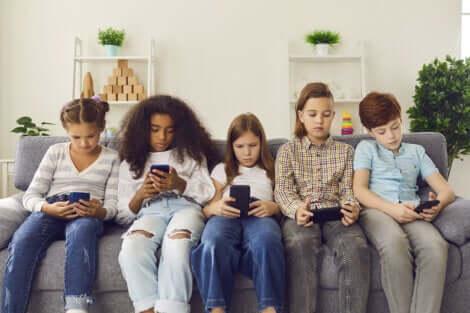 Cinq adolescents sur leur téléphone.