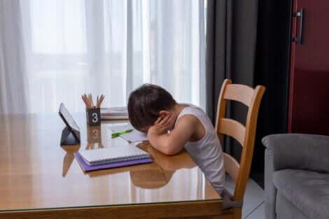Un enfant fatigué qui fait ses devoirs.