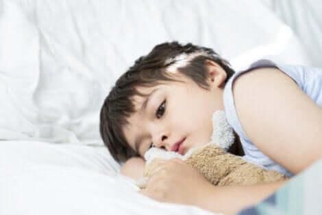 Un jeune garçon allongé avec un ours en peluche dans les bras.