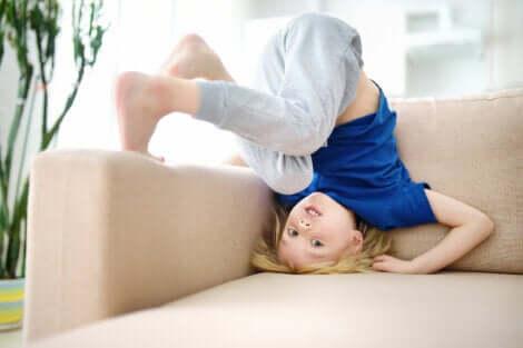 Un enfant qui se roule sur un canapé.