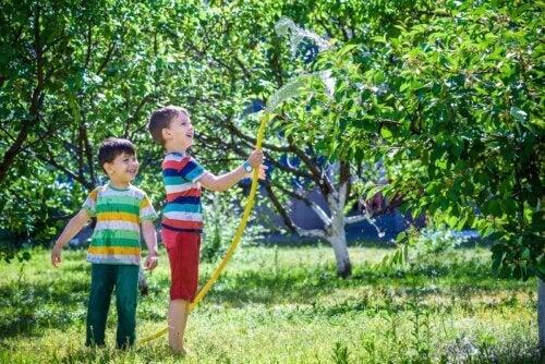 Des enfants arrosant les plantes du jardin.