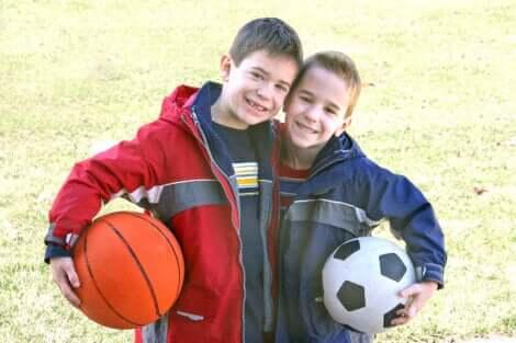 Deux enfants avec un ballon de football et de basket.