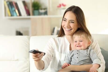 Une maman et son bébé devant la télévision.