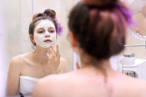 Une adolescente qui se fait un masque du visage.
