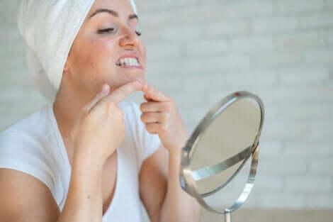 Une jeune femme qui presse un bouton devant un miroir.