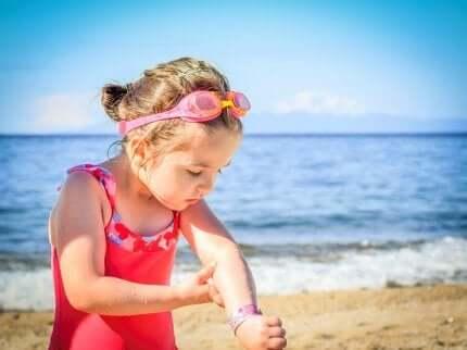 Une petite fille avec de la crème solaire.