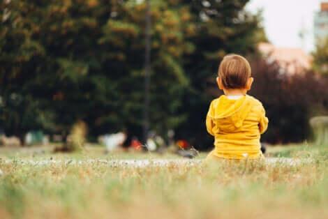Un enfant assis au parc.