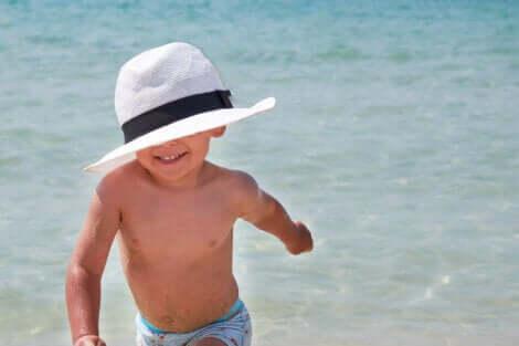 Un enfant avec un chapeau à la plage.