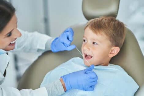 Une dentiste qui passe le fil dentaire dans la bouche d'un enfant.
