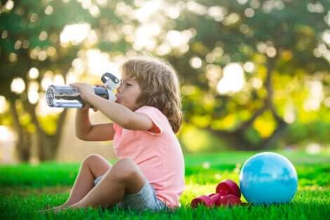 Une enfant qui boit de l'eau après avoir fait du sport.