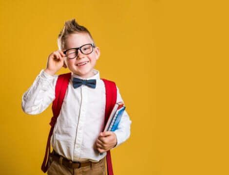 Un jeune garçon avec des lunettes et un nœud papillon.