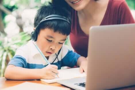 enfant écrivant devant un ordinateur