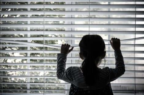 Une jeune fille qui regarde par la fenêtre.