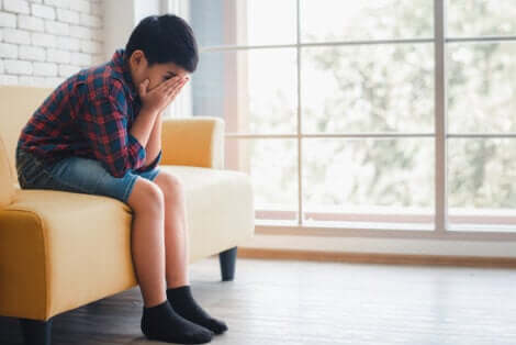 Un jeune garçon triste qui se cache le visage dans les mains.
