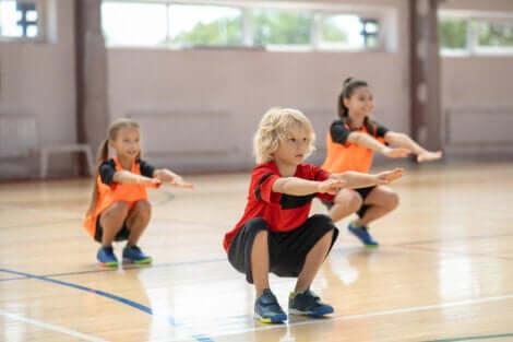 Trois enfants qui font des squats.