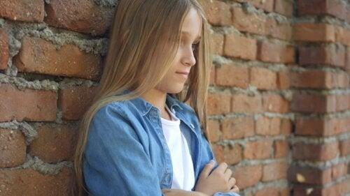 Une fille solitaire contre un mur de briques.