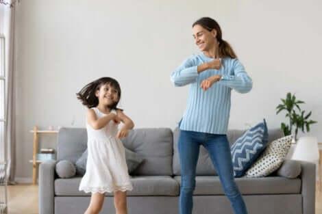 Une mère et sa fille qui dansent dans le salon.