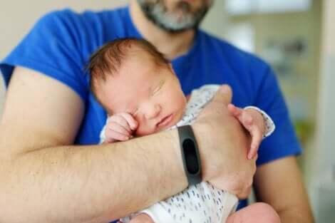 père tenant son bébé dans ses bras