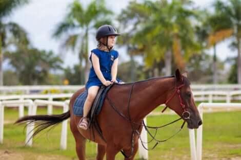 Une petite fille qui fait de l'équitation.