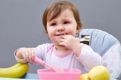 Un bébé qui mange tout seul sur sa chaise