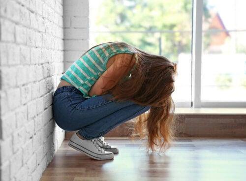 Une adolescente triste accroupie.