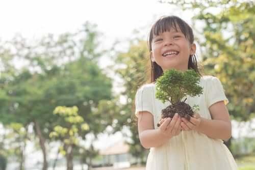 Une enfant avec un arbuste.