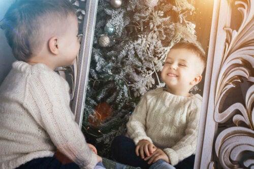 Un enfant qui parle avec le sourire dans le miroir.