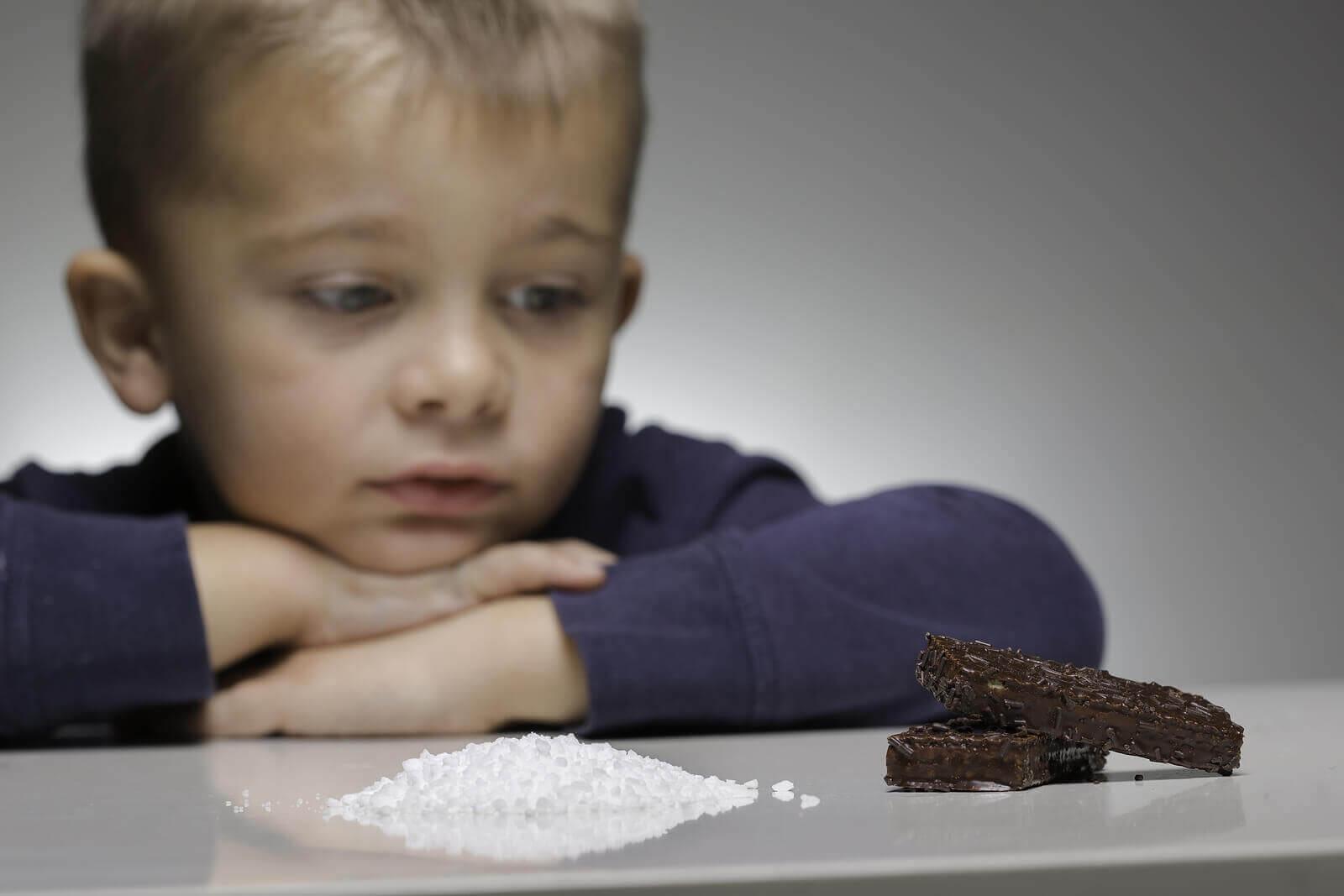 Un enfant regardant du sucre et du chocolat.