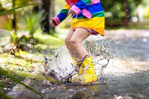 Un enfant qui saute dans une flaque d'eau et de boue.
