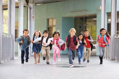 La rentrée d'école avec des enfants avec le cartable sur le dos.