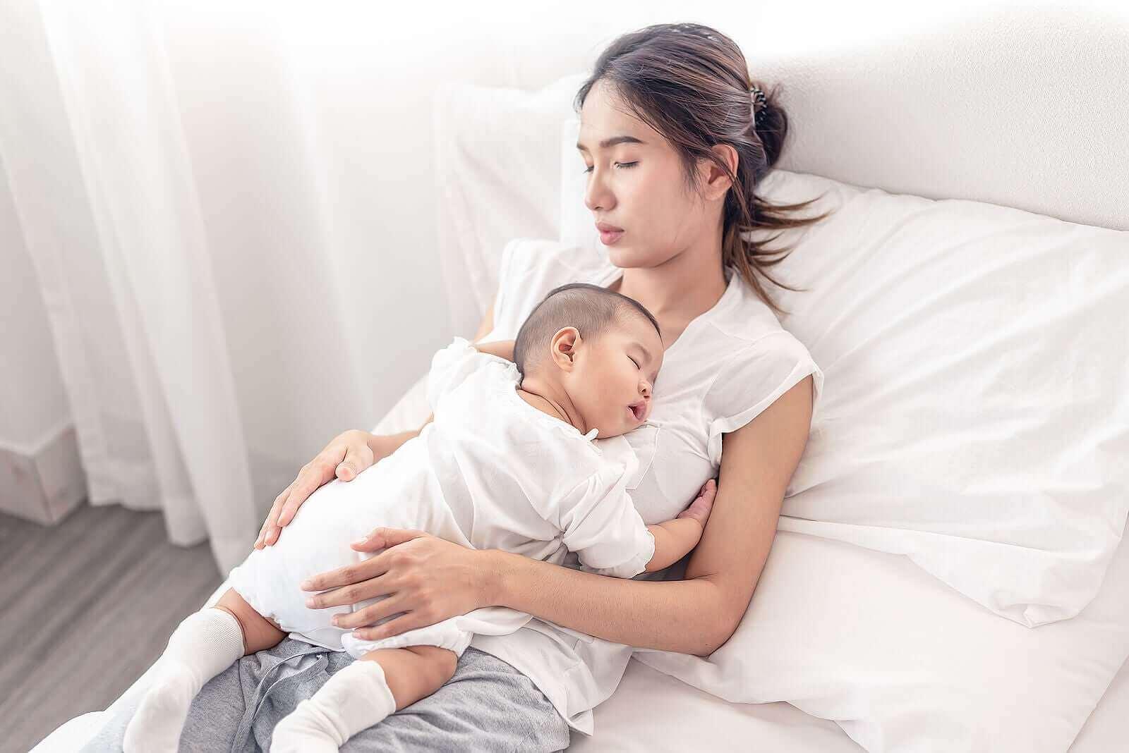 Une maman avec son enfant endormi sur le ventre.