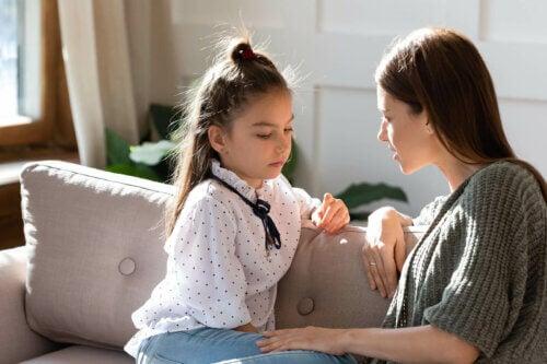 Une mère et sa fille qui parlent des sentiments sur le canapé.