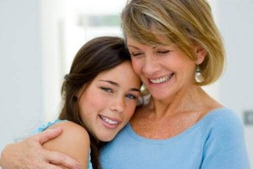 Une adolescente dans les bras de sa maman.