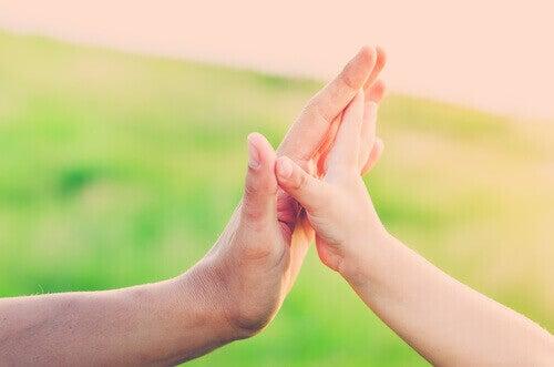 Une main d'enfant collée à une main d'adulte.