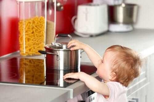 Un enfant qui touche une casserole sur les plaques de cuisson.
