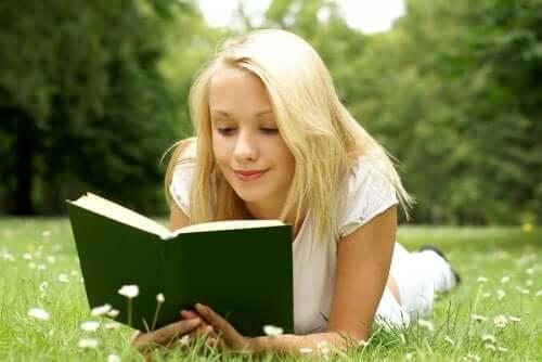 Une fille qui lit un livre dans un champ.