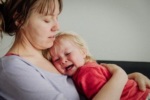 Un enfant qui pleure dans les bras de sa mère.