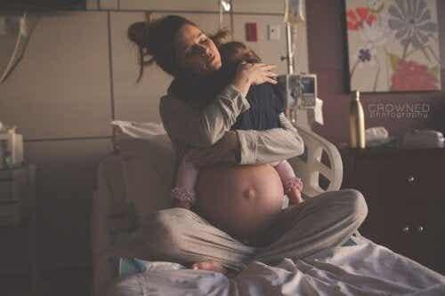 Photo émouvante : une mère serrant sa fille dans ses bras avant de se préparer à l'arrivée d'un nouveau bébé